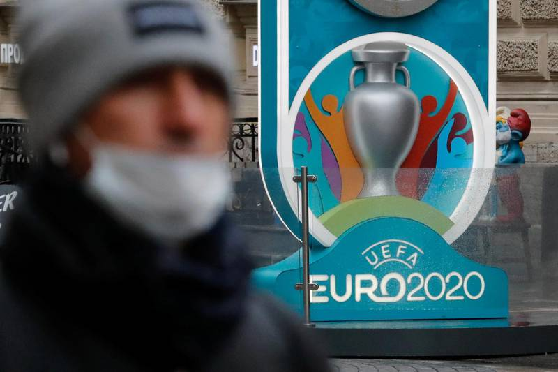 A person wearing a protective face mask walks past the Euro 2020 countdown clock, as the number of coronavirus (COVID-19) cases worldwide continues to grow, in central Saint Petersburg, Russia March 16, 2020. REUTERS/Anton Vaganov