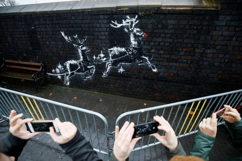 People gather round a new mural by the street artist Banksy in Birmingham, Britain, December 10, 2019.  REUTERS/Henry Nicholls  NO RESALES. NO ARCHIVES