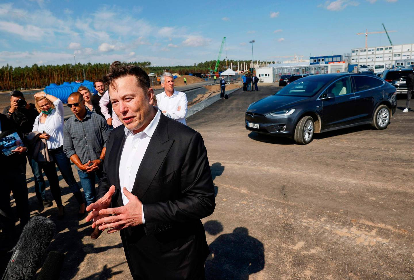 """Tesla CEO Elon Musk talks to media as he arrives to visit the construction site of the future US electric car giant Tesla, on September 03, 2020 in Gruenheide near Berlin. Tesla builds a compound at the site in Gruenheide in Brandenburg for its first European """"Gigafactory"""" near Berlin. / AFP / Odd ANDERSEN"""