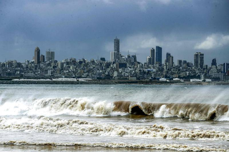 This picture taken on February 17, 2021 from the area of Dbayeh at the northern outskirts of the Lebanese capital Beirut shows waves crashing along the seashore during stormy weather with the Beirut skyline prominent in the background.  / AFP / JOSEPH EID