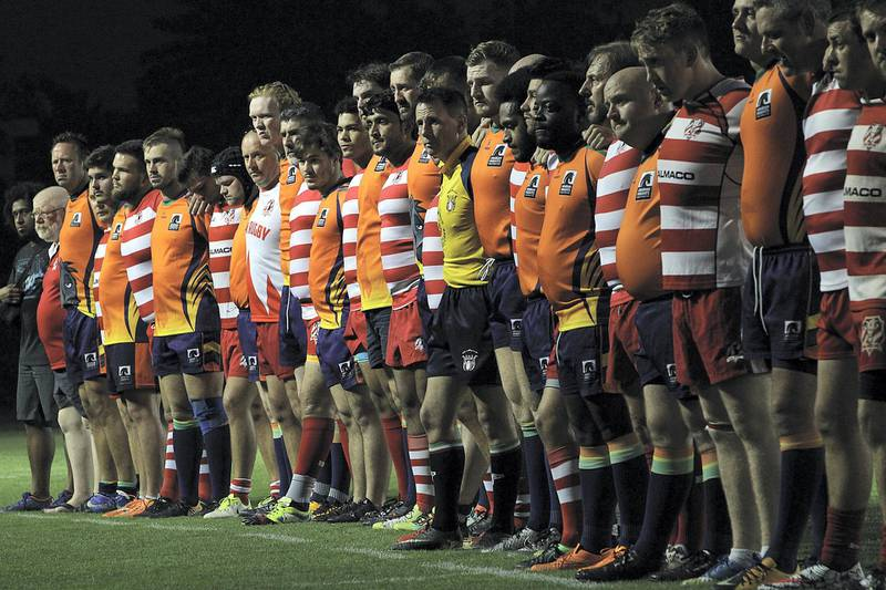 Sharjah, June, 01, 2018: RAK Rugby ( Red& White ) and  Arabian Knights ( Orange& BlacK) observes minute's silence for Nick Young, a RAK player who died after an on-field accident recently during the Nick Young Memorial match at the Sharjah Wanderers sports club in Sharjah . Satish Kumar for the National / Story by Paul Radley