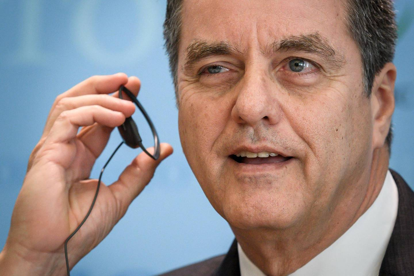 World Trade Organization (WTO) director-general Roberto Azevedo adjusts his earphone as he gives a press conference on April 12, 2018 at their headquarters in Geneva. The World Trade Organization releases today its latest forecasts as trade tensions between the United States and China ratchet up. / AFP PHOTO / Fabrice COFFRINI