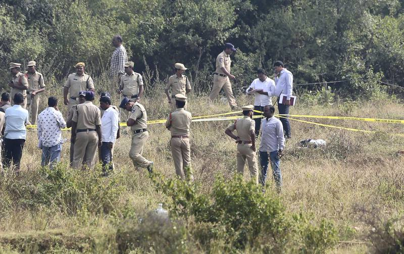 Indian police officials secure the area where four men suspected of raping and killing a woman were killed in Shadnagar some 50 kilometers or 31 miles from Hyderabad, India, Friday, Dec. 6, 2019. Indian police on Friday fatally shot and killed four men suspected of raping and killing a woman in southern India, leading some to celebrate their deaths as justice in a case that has sparked protests across the country. (AP Photo/Mahesh Kumar A.)