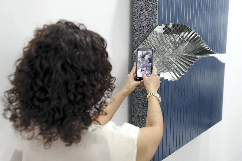 Dubai, United Arab Emirates - Reporter: Alexandra Chaves. Arts and Lifestyle. A visitor takes a picture of Mirror 5 by Aref Montazeri. Art Dubai 2021 opens at the DIFC. Tuesday, March 30th, 2021. Dubai. Chris Whiteoak / The National