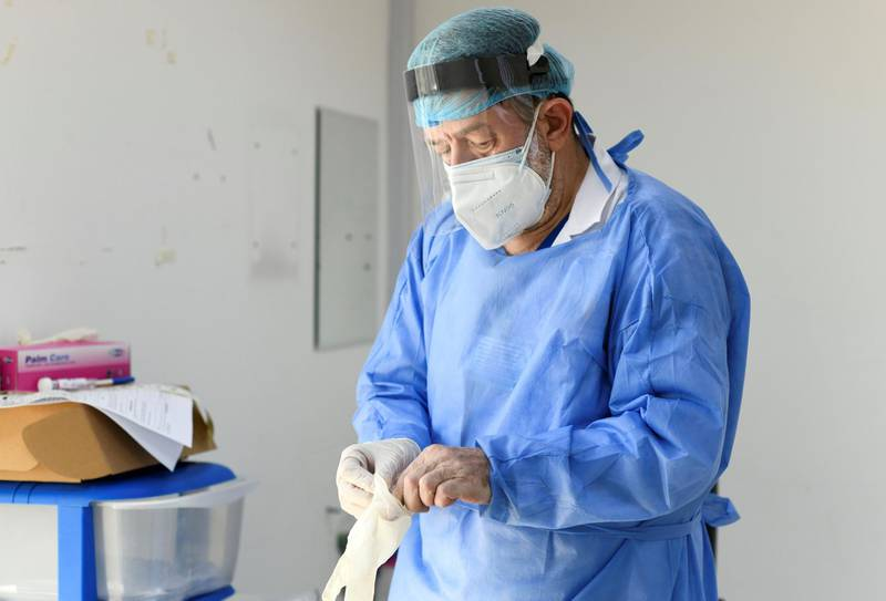 Abu Dhabi, United Arab Emirates - Medical staff prepares himself before testing the patients at Advanced Centre for Daycare Surgery. Khushnum Bhandari for The National