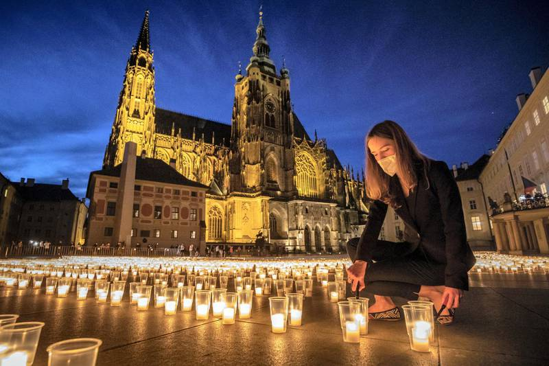 PRAGUE, CZECH REPUBLIC - MAY 10:  A woman lights a candle to commemorate victims of the COVD-19 pandemic at the Prague Castle on May 10, 2021 in Prague, Czech Republic. People commemorated almost 30.000 victims of covid-19 in the country at the Prague Castle during the largest act of reverence in the history of the Prague Castle. The daily numbers of newly confirmed positive COVID-19 cases continue to decline in the Czech Republic. (Photo by Gabriel Kuchta/Getty Images)