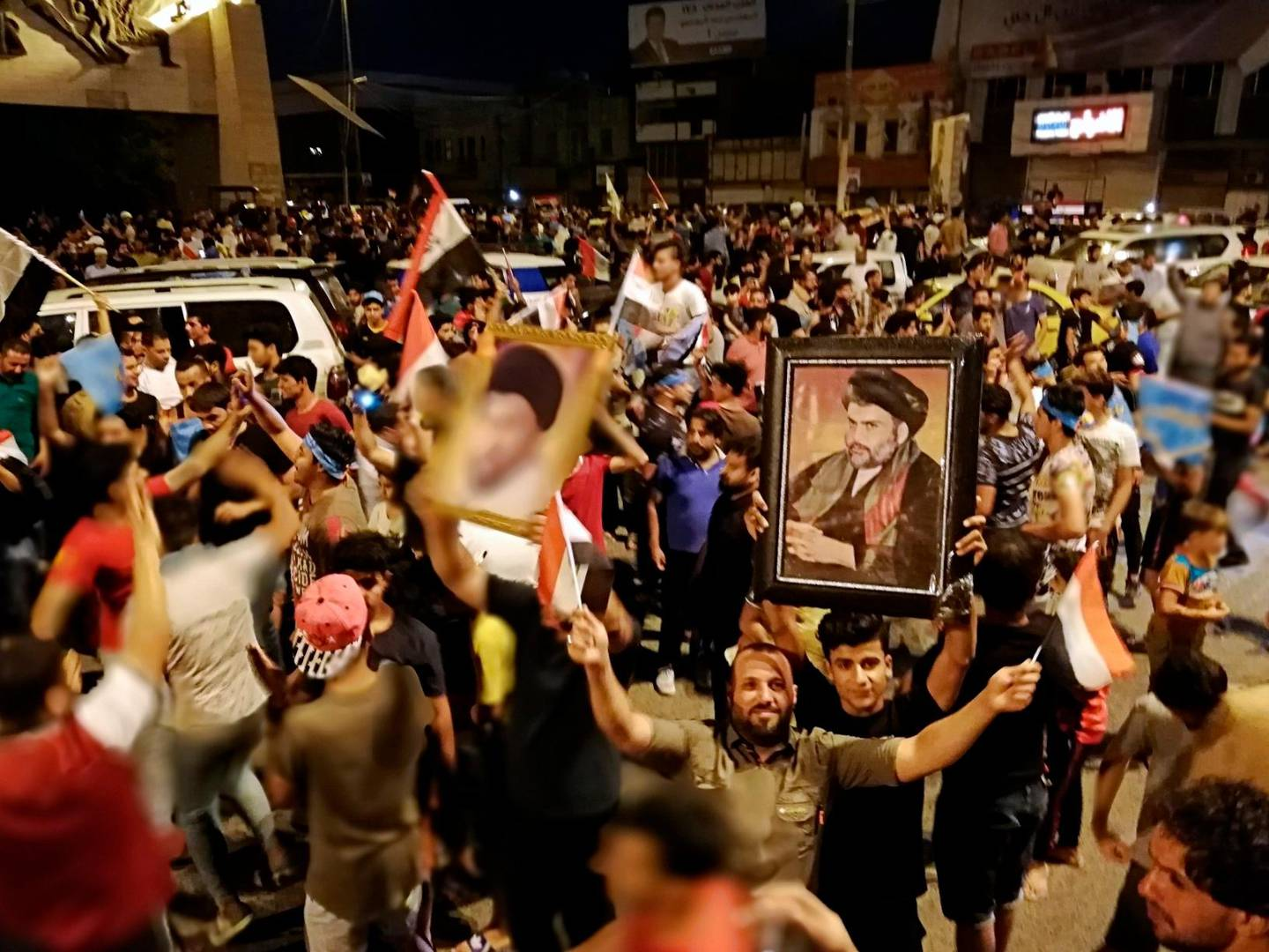 Followers of Shiite cleric Muqtada al-Sadr, seen in the posters, celebrate after the preliminary results of the parliamentary elections are announced, in Tahrir Square, Baghdad, Iraq, early Monday, May 14, 2018. (AP Photo/Hadi Mizban)