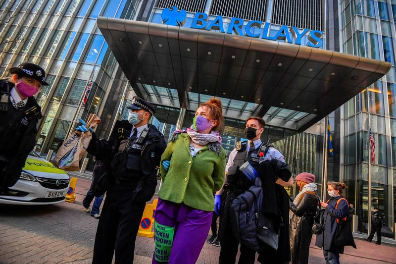 Police officers detain an activist from the Extinction Rebellion, a global environmental movement, outside the Barclays offices in Canary Wharf, London, Britain, April 7, 2021. REUTERS/Toby Melville