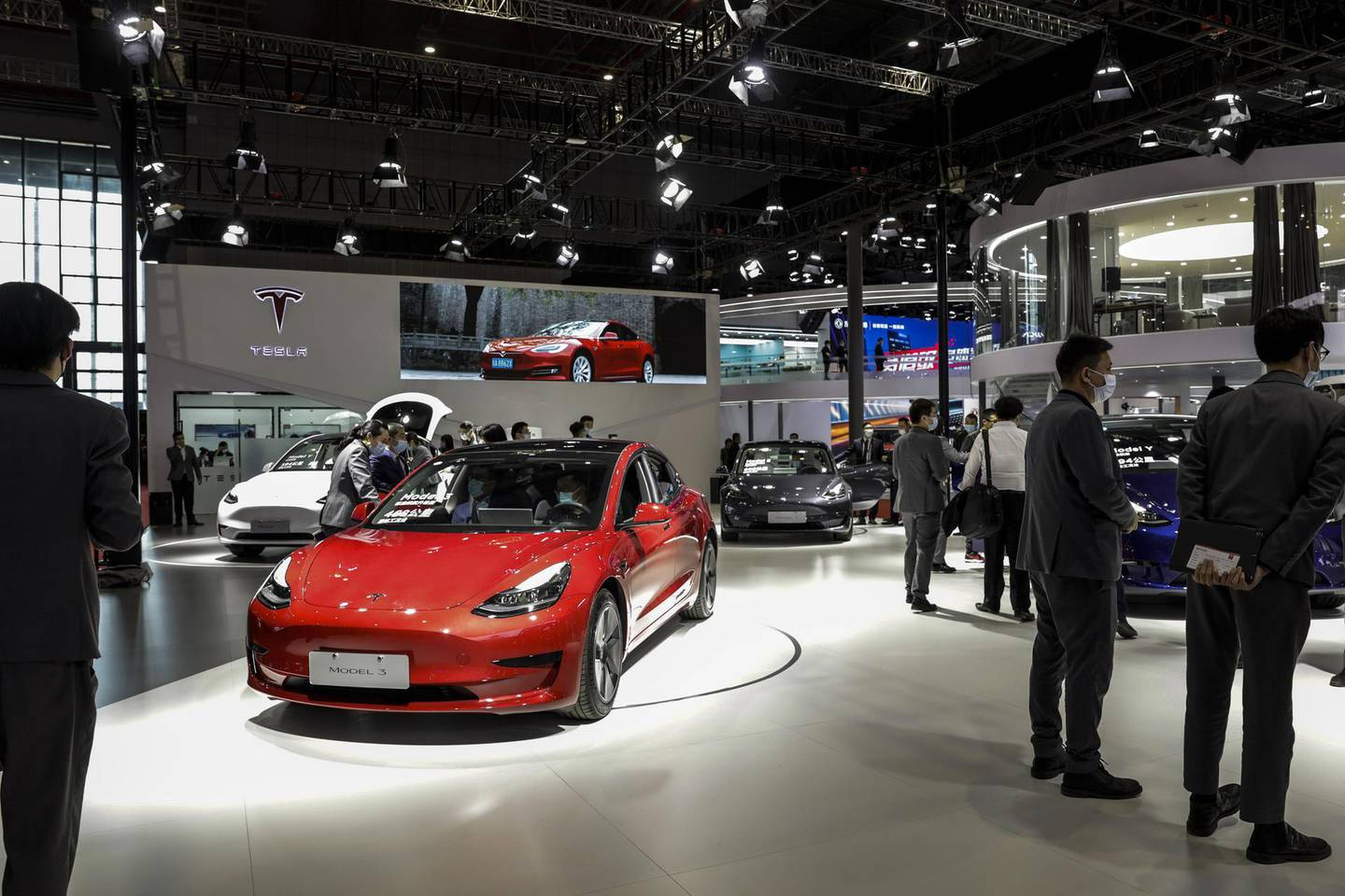 Visitors walk past Chinese-made Tesla Inc. electric vehicles at the company's booth at the Auto Shanghai 2021 show in Shanghai, China, on Monday, April 19, 2021. The Shanghai International Automobile Industry Exhibition kicked off on Monday in China's financial hub, a multiday event aimed at showcasing the best and brightest car innovations in the world's biggest vehicle market. Photographer: Qilai Shen/Bloomberg