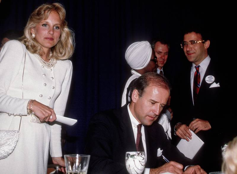 American educator Dr Jill Biden (left) stands behind her husband, American politician US Senator (and future Vice President) Joe Biden, as he signs autographs after his keynote address to an Illinois Democratic Party Unity Dinner, Chicago, Illinois, May 11, 1987. (Photo by Mark Reinstein/Corbis via Getty Images)