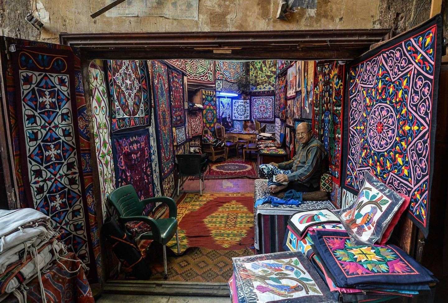 An Egyptian craftsman sits working on a tapestry in his shop in Khayamiya Street, or the Street of Tent-makers, in the old city of the Egyptian capital Cairo on December 18, 2018. Along the sides of the roofed street of Khayamiya, or the Street of Tent-makers, dozens of craftsmen's shops have drawn foreign visitors for years until the 2011 uprising toppled longtime ruler Hosni Mubarak after which business has slowed to a trickle. The centuries-old art of Khayamiya, belived to have emerged during the Fatimid dynasty (10th-12th century AD), goes back to the time of travelling caravans, when huge tent pavilions were used as shields from the desert's searing sun. / AFP / Mohamed el-Shahed