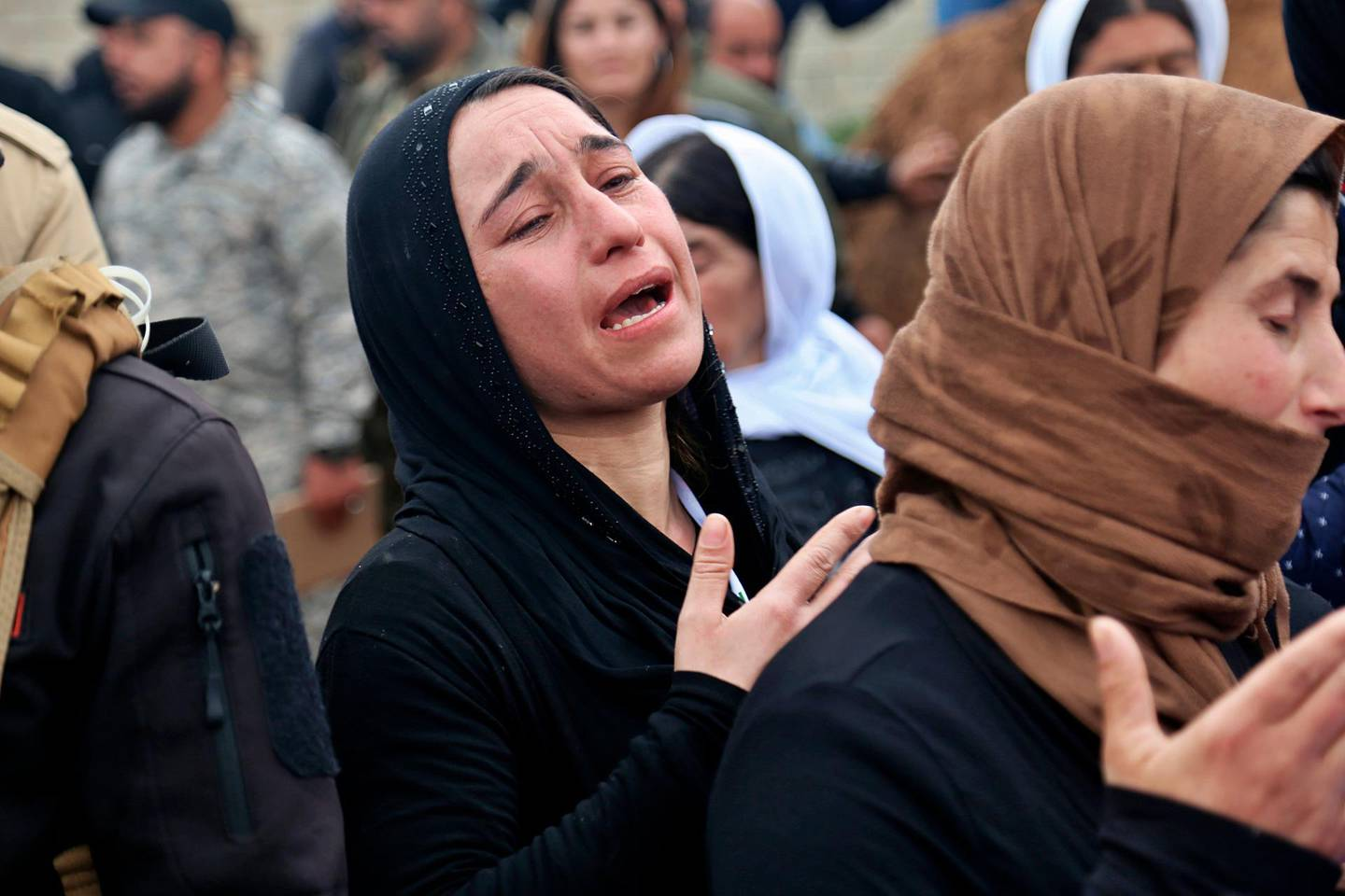 In this Friday, March 15, 2019 picture, Iraqi Yazidi women mourn during exhumation process of a mass grave in Iraq's northwestern region of Sinjar. The Iraqi government with U.N. support has started the exhumation process of the mass graves in Iraq's northwestern region of Sinjar.  (AP Photo/Farid Abdulwahed)