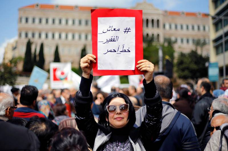 """A protester holds a placard with Arabic that reads, """"Salary of the poor is a red line,"""" in front of the government building during a parliament session to approve a plan to restructure the country's electricity sector, in Beirut, Lebanon, Wednesday, April 17, 2019. State employees fear they could have their salaries cut as the government discusses austerity measures to avoid a financial and economic crisis. (AP Photo/Bilal Hussein)"""