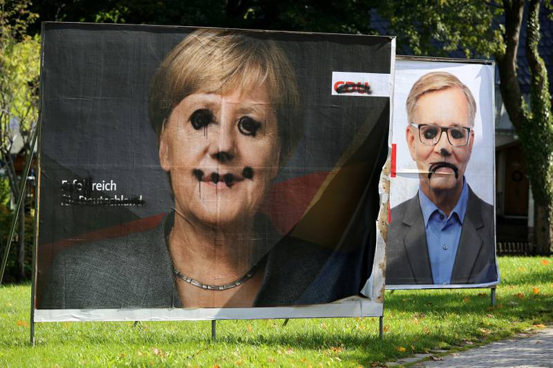 Defaced election campaign posters of Angela Merkel's Christian Democratic Union CDU and of Die Linke party are pictured in Altenberg, Germany, September 27, 2017. Picture taken September 27, 2017.       REUTERS/Matthias Schumann