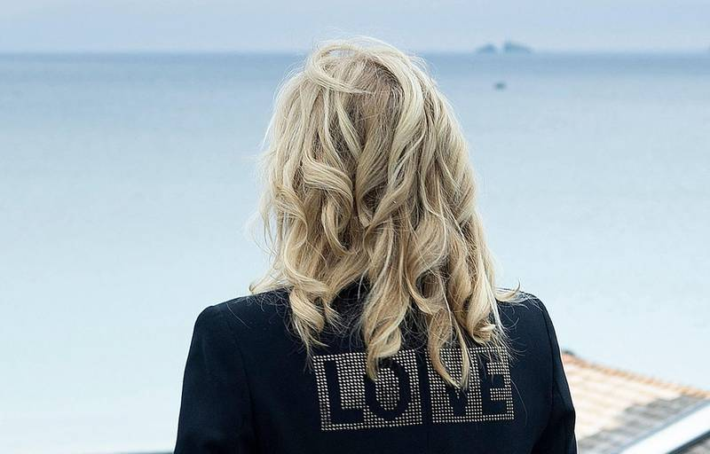 TOPSHOT - US First Lady Jill Biden, wearing a jacket with the words 'love' on the back, poses for a photograph looking out over the sea, at Carbis Bay, in Cornwall on June 10, 2021, ahead of the three-day G7 summit being held from 11-13 June.  G7 leaders from Canada, France, Germany, Italy, Japan, the UK and the United States meet this weekend for the first time in nearly two years, for the three-day talks in Carbis Bay, Cornwall. -   / AFP / Brendan Smialowski