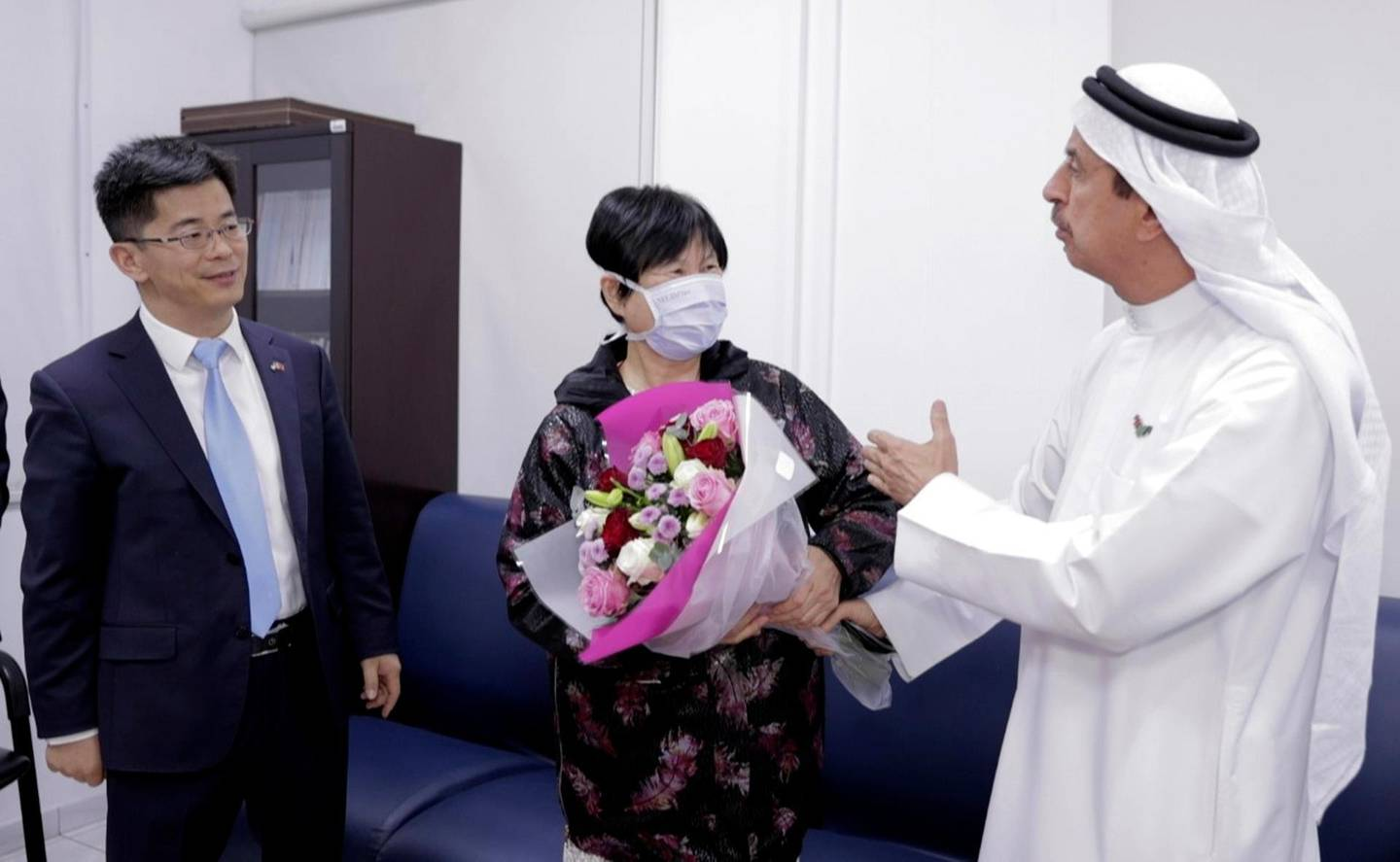 """Liu Yujia, center, receives a bouquet of flowers from Dr. Hussein Al Rand, an under-secretary at the Ministry of Health, after she tested negative for the Coronavirus, as Consul General Li Xuhang of China looks on, in Abu Dhabi, United Arab Emirates, Sunday, Feb. 9, 2020. The state-run WAM news agency announced Sunday night that 73-year-old Chinese national Liu Yujia, one of the people infected with the new coronavirus in the Arabian Peninsula nation, """"has recovered."""" (WAM via AP)"""