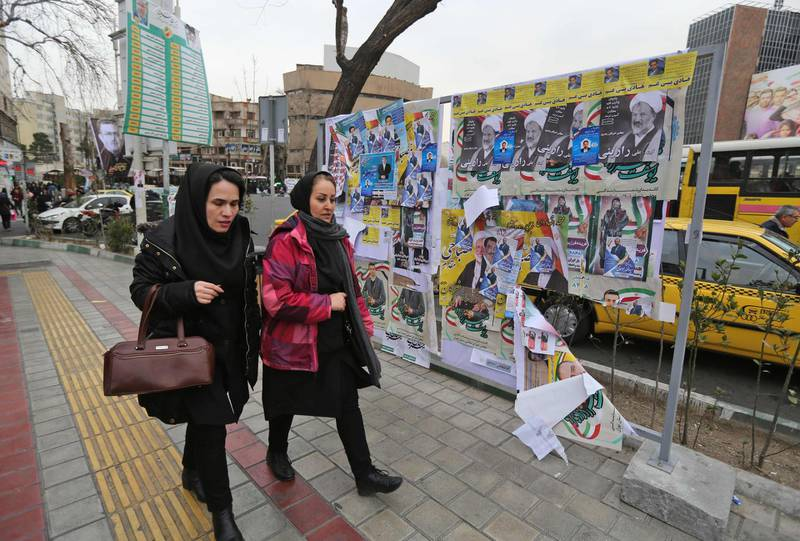 Iranian women walk past electoral posters and fliers during the last day of election campaign in Tehran on February 19, 2020. Iran's electoral watchdog today defended its decision to disqualify thousands of candidates for a crucial parliamentary election in two days, as a lacklustre campaign neared its end. Conservatives are expected to make an overwhelming resurgence in Friday's election, which comes after months of steeply escalating tensions between Iran and its decades-old arch foe the United States. / AFP / ATTA KENARE