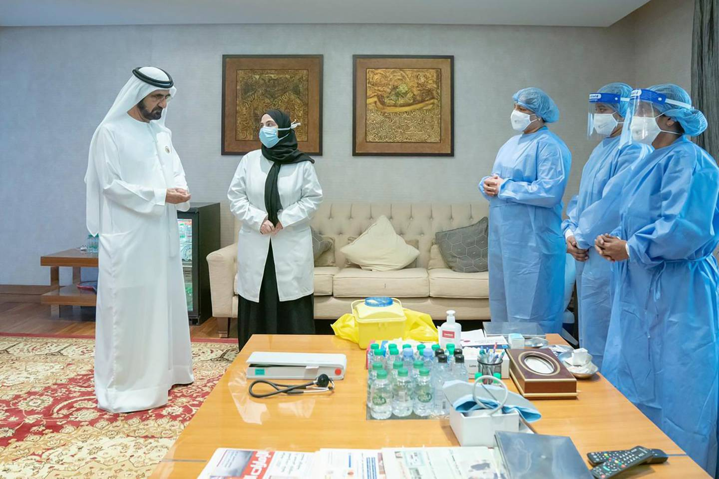 """A handout image provided by United Arab Emirates News Agency (WAM) on November 3, 2020 shows Dubai's Ruler Crown Prince of Dubai Sheikh Mohammed bin Rashid Al-Maktoum (L) before receiving an injection of a COVID-19 coronavirus vaccine. Dubai's ruler has received an experimental coronavirus vaccine, according to his Twitter account on November 3, as global cases remain on the rise. Sheikh Mohammed -- who is also prime minister of the United Arab Emirates -- is the latest in a string of Gulf officials who have been injected by an experimental drug that could help bring the pandemic to an end. Chinese drug giant Sinopharm began the third phase of trials for a Covid-19 vaccine in the United Arab Emirates in July, with Emirati officials saying the results have been positive. - === RESTRICTED TO EDITORIAL USE - MANDATORY CREDIT """"AFP PHOTO / HO / WAM"""" - NO MARKETING NO ADVERTISING CAMPAIGNS - DISTRIBUTED AS A SERVICE TO CLIENTS ===  / AFP / - / === RESTRICTED TO EDITORIAL USE - MANDATORY CREDIT """"AFP PHOTO / HO / WAM"""" - NO MARKETING NO ADVERTISING CAMPAIGNS - DISTRIBUTED AS A SERVICE TO CLIENTS ==="""