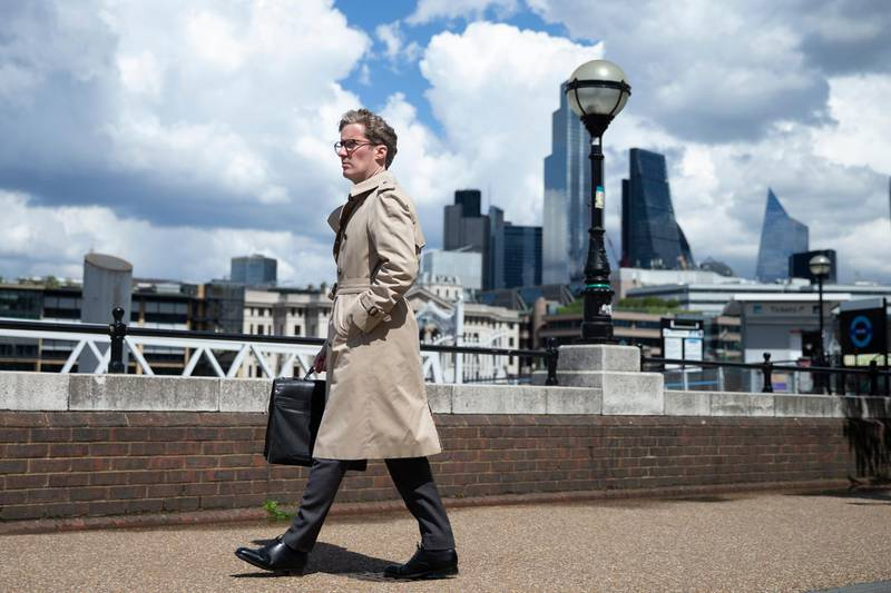 LONDON, ENGLAND - MAY 19: A pedestrian wearing a trench coat walks along South Bank in view of the City of London skyline on May 19, 2021 in London, England. Although indoor drinking and dining were permitted in England with yesterday's Covid-19 lockdown easing, there remain social distancing rules and restrictions on party size that prevent many restaurants from returning to full capacity. The next phase of reopening, when all limits on social contact are due to be lifted on June 21, is vital to the recovery of the hospitality business. (Photo by Hollie Adams/Getty Images)