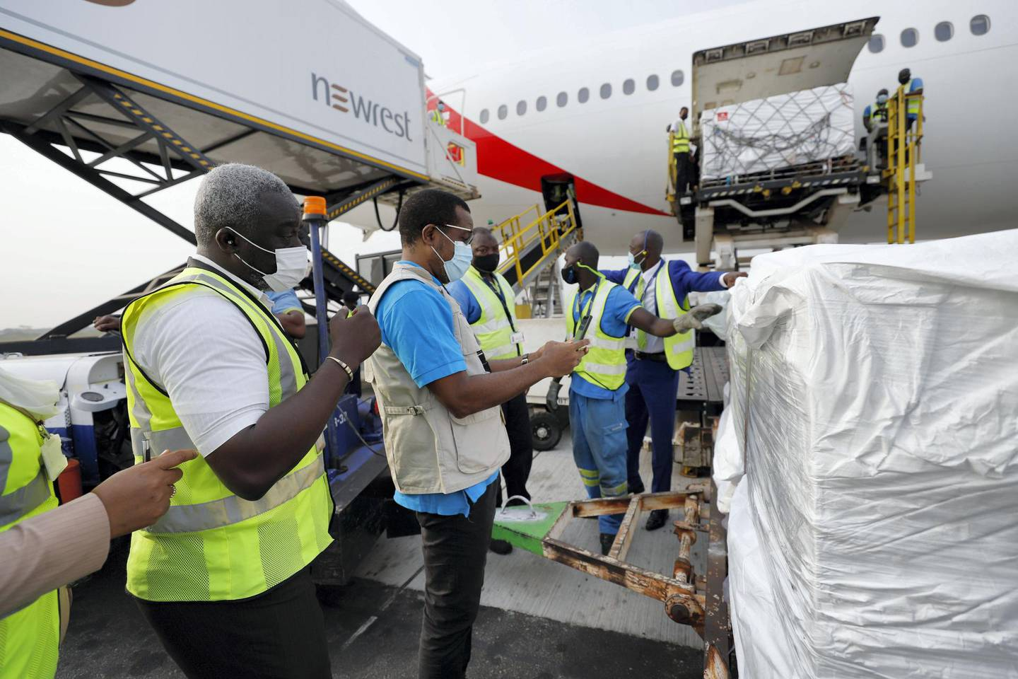 """On 24 February 2021, staff unloads the first shipment of COVID-19 vaccines distributed by the COVAX Facility at the Kotoka International Airport in Accra, Ghana's capital.   The shipment with 600 doses of the vaccine also represents the beginning of what should be the largest vaccine procurement and supply operation in history. The COVAX Facility plans to deliver close to 2 billion doses of COVID-19 vaccines this year. This is an unprecedented global effort to make sure all citizens have access to vaccines. Anne-Claire Dufay UNICEF UNICEF Representative in Ghana and WHO country representative Francis Kasolo said in a joint statement: After a year of disruptions due to the COVID-19 pandemic, with more than 80,700 Ghanaians getting infected with the virus and over 580 lost lives, the path to recovery for the people of Ghana can finally begin.  """"This is a momentous occasion, as the arrival of the COVID-19 vaccines into Ghana is critical in bringing the pandemic to an end,""""   These 600,000 COVAX vaccines are part of an initial tranche of deliveries of the AstraZeneca / Oxford vaccine licensed to the Serum Institute of India, which represent part of the first wave of COVID vaccines headed to several low and middle-income countries. """"The shipments also represent the beginning of what should be the largest vaccine procurement and supply operation in history. The COVAX Facility plans to deliver close to 2 billion doses of COVID-19 vaccines this year. This is an unprecedented global effort to make sure all citizens have access to vaccines. """"We are pleased that Ghana has become the first country to receive the COVID-19 vaccines from the COVAX Facility. We congratulate the Government of Ghana – especially the Ministry of Health, Ghana Health Service, and Ministry of Information - for its relentless efforts to protect the population. As part of the UN Country Team in Ghana, UNICEF and WHO reiterate our commitment to support the vaccination campaign and contain the spread"""