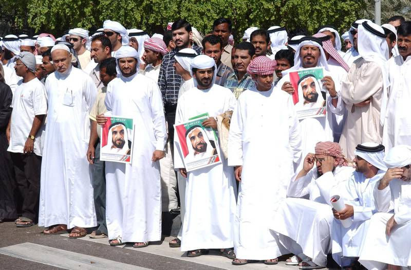Abu Dhabi, UAE. November 3 2004. A crowd of mourners watch the funeral convoy of Sheikh Zayed as it departs the Sultan Bin Zayed mosque in Bateen, where prayers were offered, and drives to the Sheikh Zayed mosque for the burial ceremony.   (C) Al Ittihad