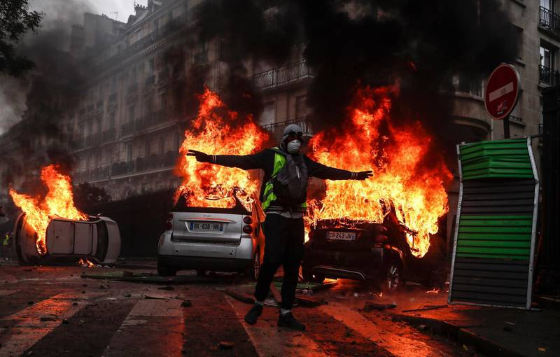 epa07248897 YEARENDER DECEMBER 2018  Protesters wearing yellow vests (gilets jaunes) set cars and barricade on fire as they clash with riot police on Avenue Foch near the Arc de Triomphe during a demonstration over high fuel prices on the Champs Elysee in Paris, France, 01 December 2018. The so-called 'gilets jaunes' (yellow vests) are a protest movement, which reportedly has no political affiliation, that is protesting across the nation over high fuel prices.  EPA/ETIENNE LAURENT