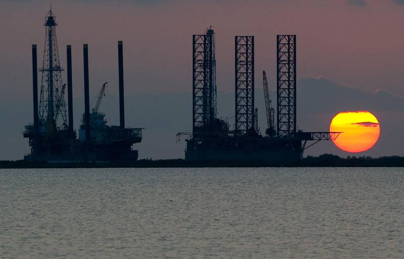 """(FILES) In this file photo taken on June 13, 2010, the sun sets behind two offshore oil platform under construction in Port Fourchon, Louisiana. Stored in a complex of four underground sites along the coasts of the Gulf of Texas and Louisiana, the US strategic oil reserves are currently 660 million barrels for a total storage capacity of 727 million barrels. The US government plans to sell between 5 and 30 million barrels of oil from these strategic reserves (SPR), according to Bloomberg. / AFP / Saul LOEB / TO GO WITH AFP STORY by Ali BEKHTAOUI, """"Strategic oil reserves, a multipurpose weapon"""""""
