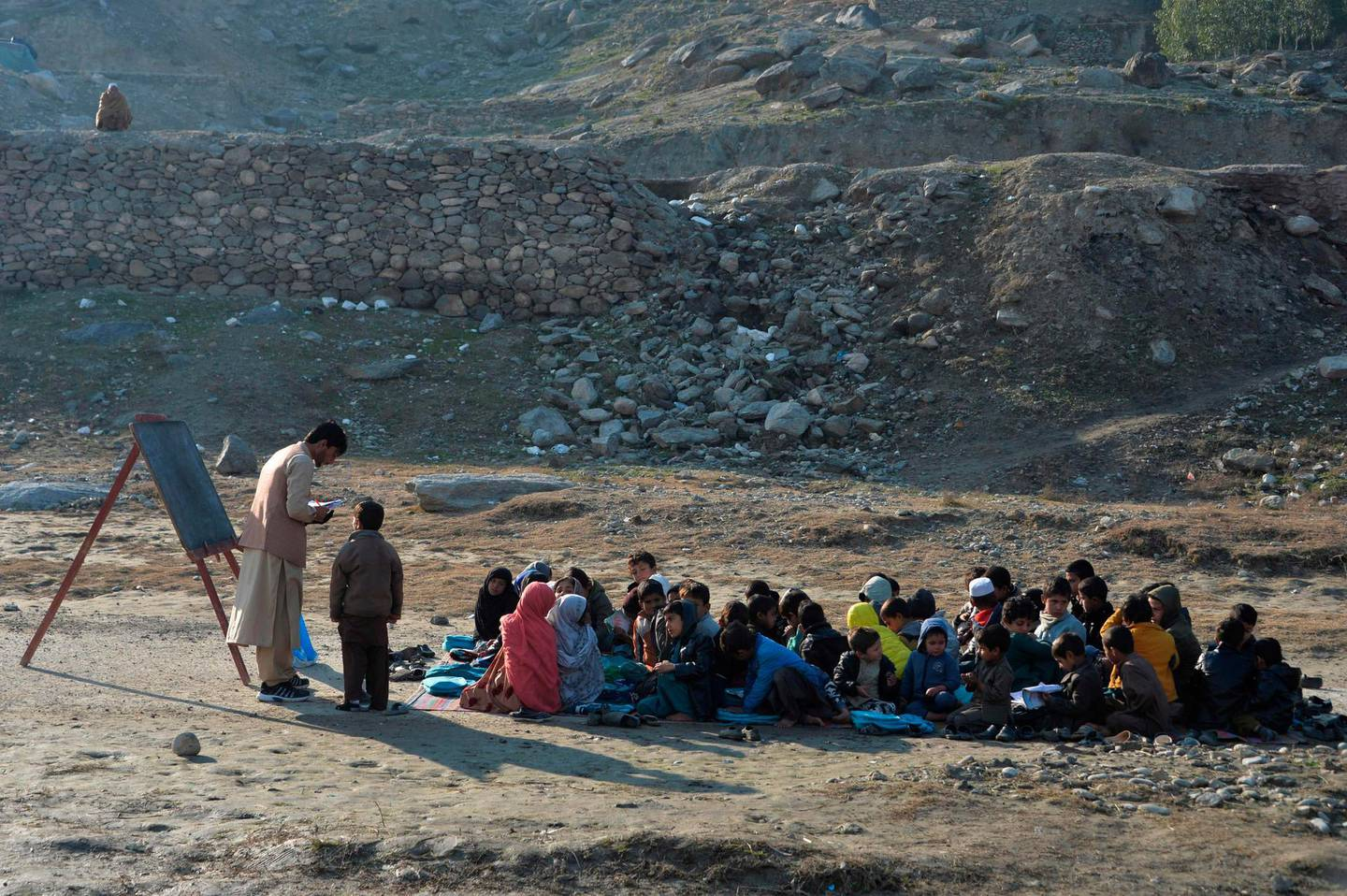 School children take part in a lesson in an open-air classroom in Qarghayi district of Laghman Province on January 20, 2020. / AFP / NOORULLAH SHIRZADA