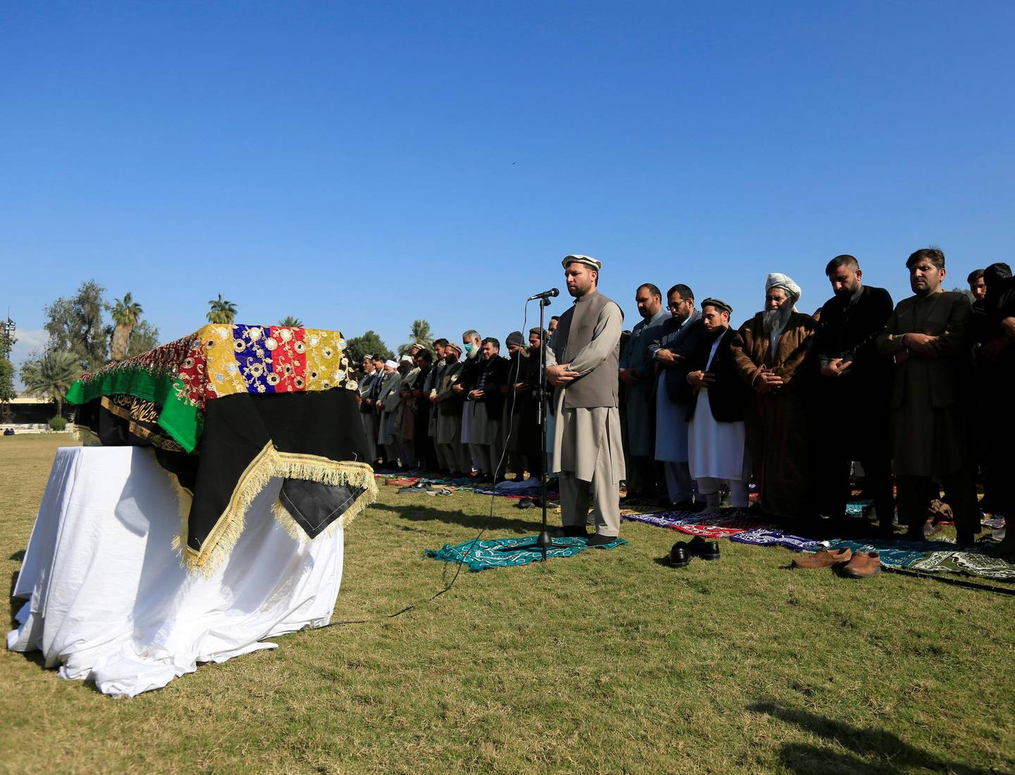 Afghan men pray near the coffin of journalist Malalai Maiwand, who was shot and killed by unknown gunmen in Jalalabad, Afghanistan December 10, 2020. REUTERS/Parwiz