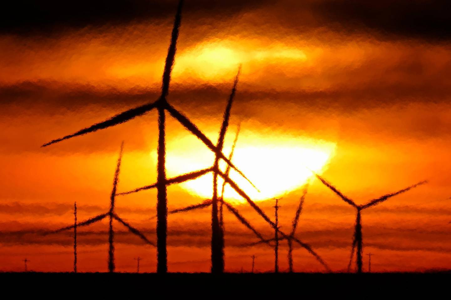 Wind turbines are silhouetted against the rising sun Wednesday, Jan. 13, 2021, near Spearville, Kan. (AP Photo/Charlie Riedel)