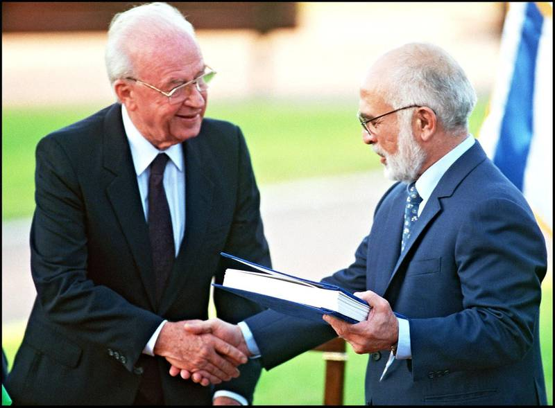 (FILES) Hussein Ibn Talal, King of Jordan (r) and Israeli Premier Yitzhak Rabin (l) shake hands after they exchanged the documents of the Peace Treaty at Beit Gabriel conference center 10 November 1994 on the southern shore of the Sea of Galilee. (Photo by SVEN NACKSTRAND / AFP FILES / AFP)