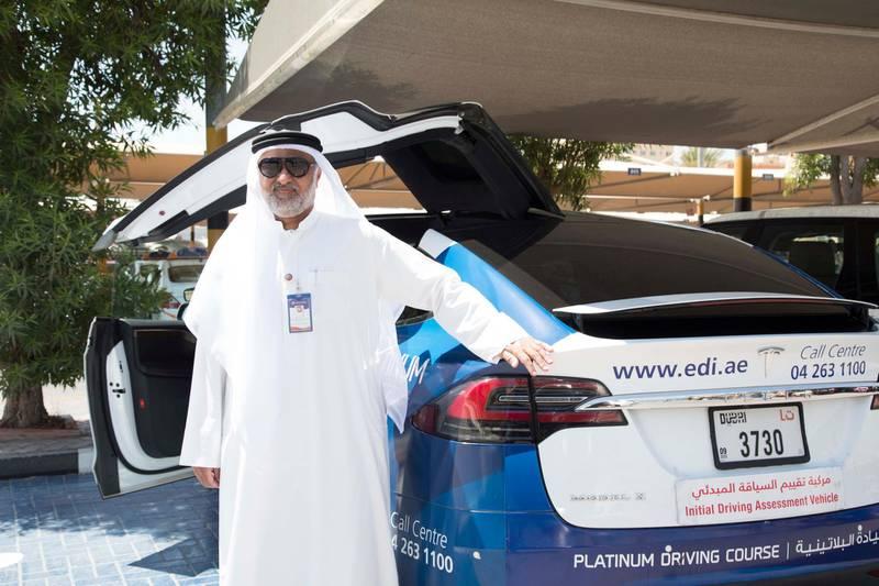 Dubai, United Arab Emirates - Taleb Mahmoud Ayub, Head of Operations next to a Tesla car at the Emirates Driving Institute, Dubai.  Leslie Pableo for The National