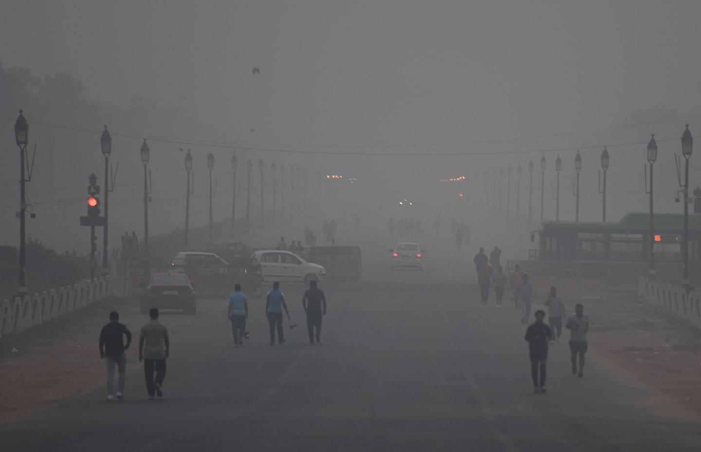 (FILES) In this file photo taken on November 2, 2018 Indian pedestrians walk amid heavy smog conditions in New Delhi. Residents of the Indian capital New Delhi lose on average ten years off their life expectancy due to the catastrophic effect of the city's air pollution, compared to their expected life longevity if they were breathing healthy air, according to a study published by the University of Chicago on November 19. / AFP / Money SHARMA