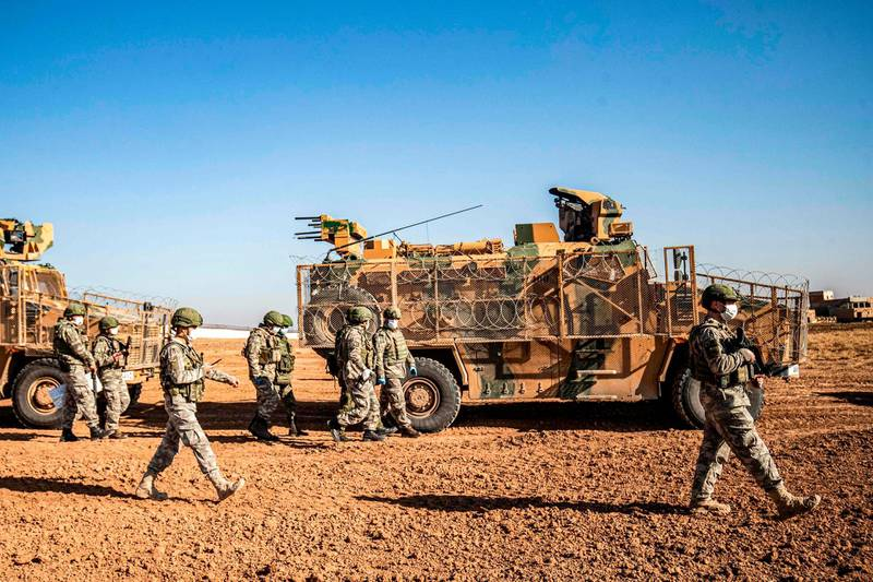 Turkish soldiers are pictured next to a military convoy during a joint Russian-Turkish patrol in the eastern countryside of the town of Darbasiyah near the border with Turkey in Syria's northeastern Hasakah province on December 7, 2020.  / AFP / Delil SOULEIMAN