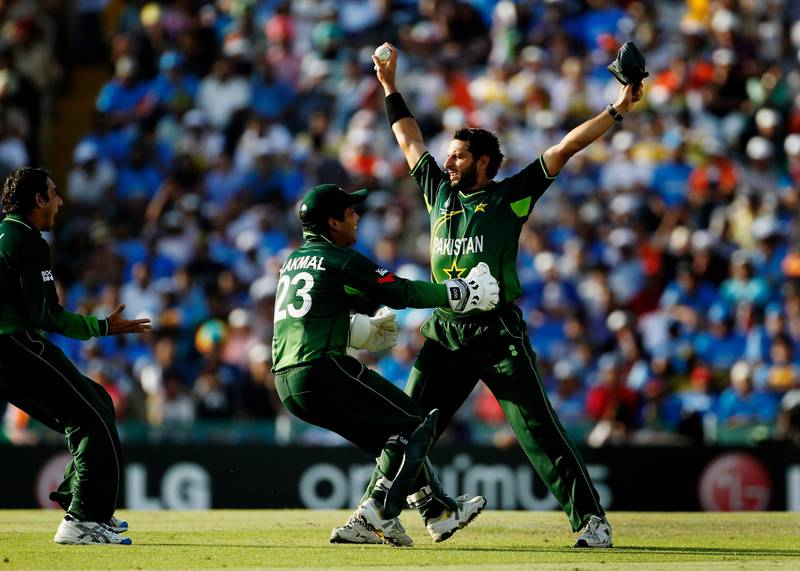 MOHALI, INDIA - MARCH 30:  Captain Shahid Afridi of Pakistan celebrates with team mates Kamran Akmal and Saeed Ajmal after taking the catch to dismiss Sachin Tendulkar of India off the bowling of Saeed Ajmal of Pakistan during the 2011 ICC World Cup second Semi-Final between India and Pakistan at Punjab Cricket Association (PCA) Stadium on March 30, 2011 in Mohali, India.  (Photo by Daniel Berehulak/Getty Images)