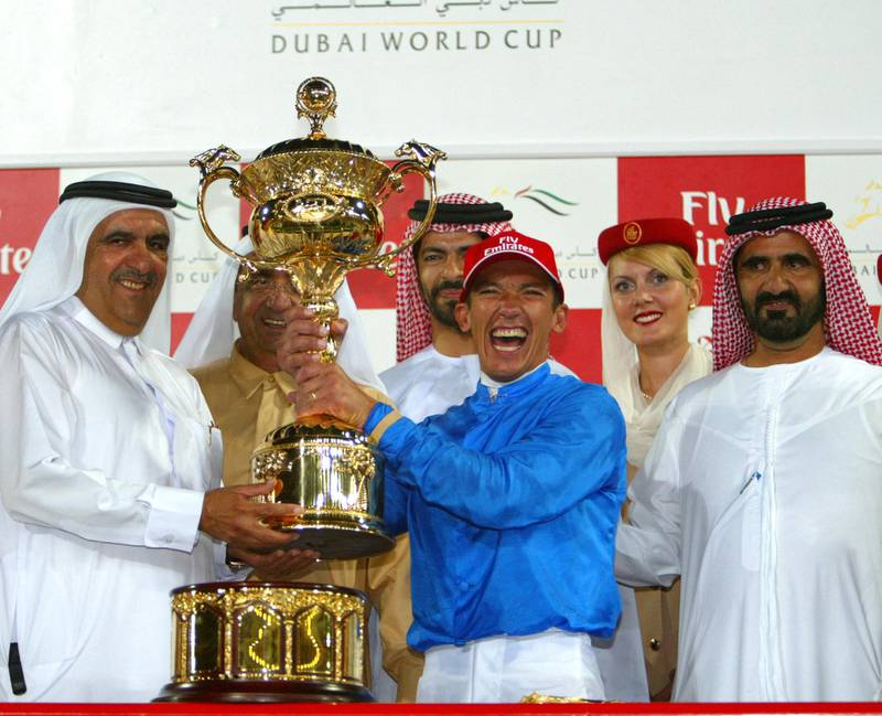 Italian rider Frankie Dettori celebrates victory at the Dubai World Cup, 29 March 2003, with Sheikh Mohammed Bin Rashed al-Maktoum (R) UAE's Minister of Defence and Crown Prince of Dubai; Sheikh Maktoum bin Rashed al-Maktoum (2nd from L), UAE's Prime Minister and ruler of Dubai; Sheikh Hamdan bin Rashed al Maktoum (L), vice ruler of Dubai and trainer Saeed Bin Suroor (3rd from L). The Dubai World Cup's seven races - five group one and two group two events - at the desert emirate's Nadi al-Sheba track are worth a combined 15.25 million dollars. AFP PHOTO/JORGE FERRARI (Photo by JORGE FERRARI / AFP)