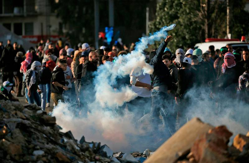 A Palestinian demonstrator throws a tear gas canister back at Israeli soldiers during clashes in Ramallah, near the Jewish settlement of Beit El, in the occupied West Bank on December 13, 2018.    A Palestinian shot dead two Israeli soldiers at a bus stop in the occupied West Bank, the military said, sparking raids in the West Bank city of Ramallah in which one Palestinian was killed. The attack came hours after security forces killed two Palestinian murder suspects, with fears of wider unrest. / AFP / ABBAS MOMANI