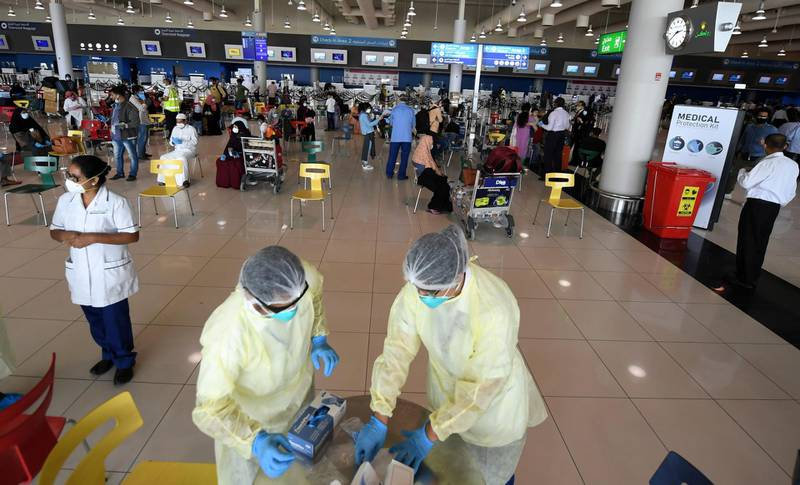 Health workers are pictured at the Dubai International Airport as travellers, including Indian nationals, leave the Gulf Emirate, on May 7, 2020, amid the novel coronavirus pandemic crisis.  The first wave of a massive exercise to bring home hundreds of thousands of Indians stuck abroad was under way today, with two flights preparing to leave from the United Arab Emirates. India banned all incoming international flights in late March as it imposed one of the world's strictest virus lockdowns, leaving vast numbers of workers and students stranded.           / AFP / Karim SAHIB