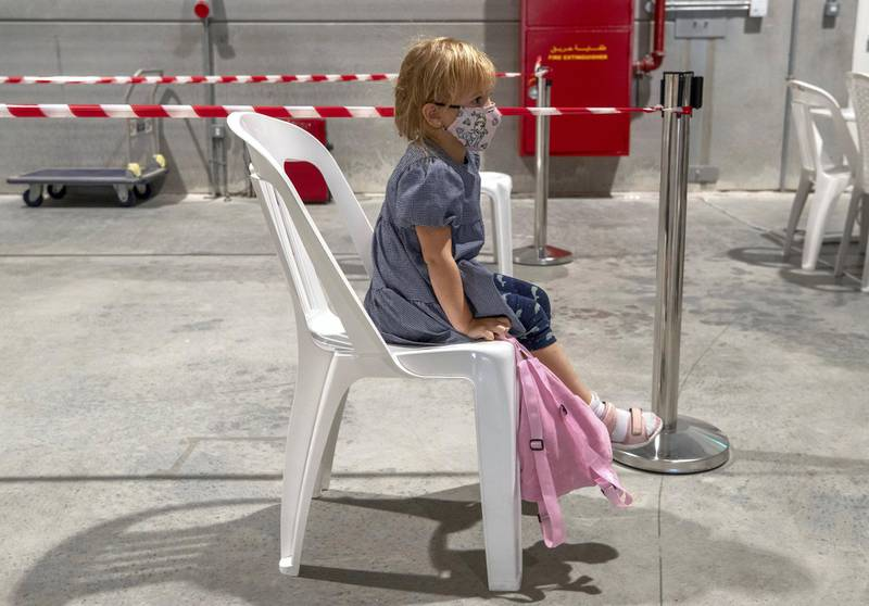 Abu Dhabi, United Arab Emirates, March 18, 2021.  A little girl waits patiently on her chair before she gets saliva tested at the Biogenix lab at G42 in Masdar City.Victor Besa/The NationalSection:  NAReporter:  Shireena Al Nowais