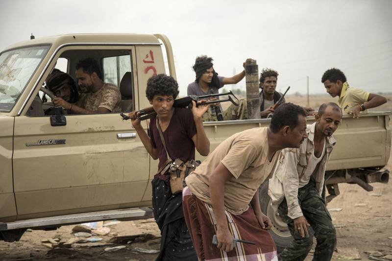 Members of the Tehama forces react  to  Houthi fighters shoot at their direction during clashes in Yemen's Hais district, Hudayda, June 2, 2018.  Photo/ Asmaa Waguih