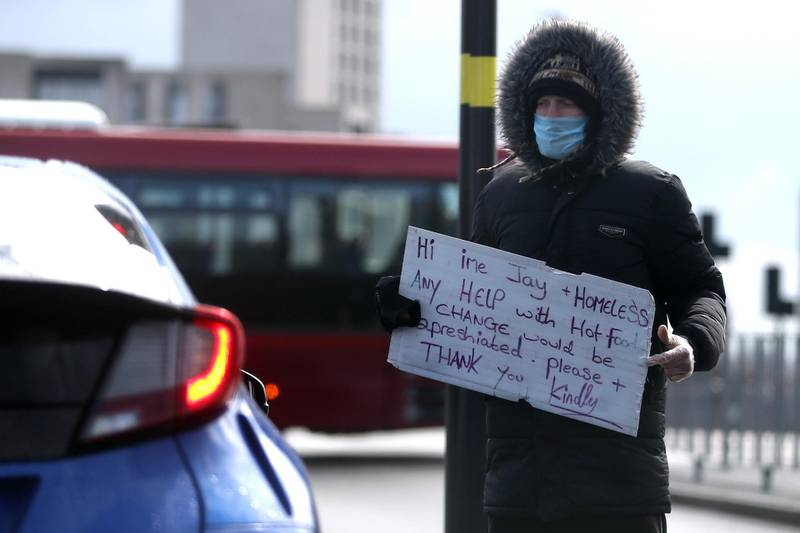 A homeless man wearing a protective face mask appeals for help to passing motorists as the spread of the coronavirus disease (COVID-19) continues, Birmingham, Britain, March 30, 2020. REUTERS/Carl Recine