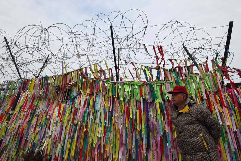 TOPSHOT - A man walks past a military fence covered with ribbons calling for peace and reunification at the Imjingak peace park near the Demilitarized Zone (DMZ) dividing the two Koreas at the border city of Paju on January 8, 2018. The two Koreas agreed last week to hold their first official dialogue in more than two years and will meet on January 9 at the border truce village of Panmunjom. / AFP PHOTO / JUNG Yeon-Je