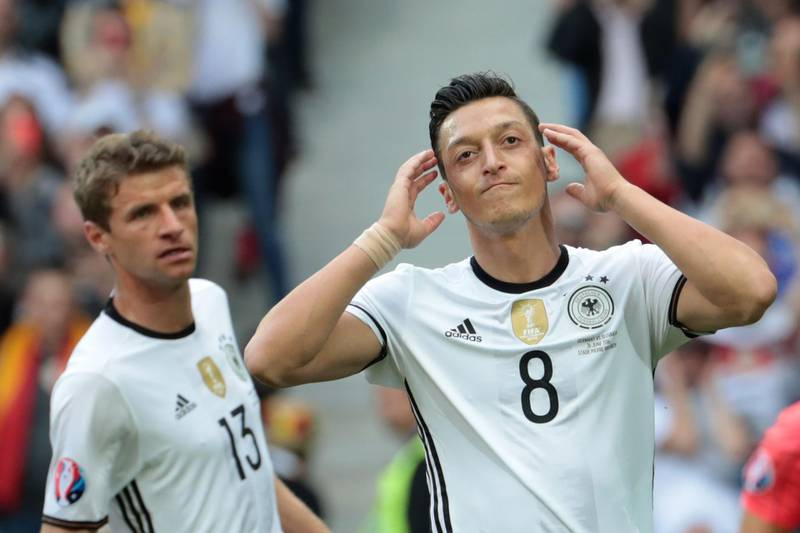 """(FILES) In this file photo taken on June 26, 2016, Germany's midfielder Mesut Oezil (R) reacts during the Euro 2016 round of 16 football match between Germany and Slovakia at the Pierre-Mauroy stadium in Villeneuve-d'Ascq near Lille on June 26, 2016. Mesut Ozil's decision to quit playing for the German national football team Die Mannschaft unleashed on July 23, 2018 a racism storm in Germany, but earned the applause of Ankara with a Turkish minister hailing """"a goal against the virus of fascism"""". / AFP / KENZO TRIBOUILLARD"""
