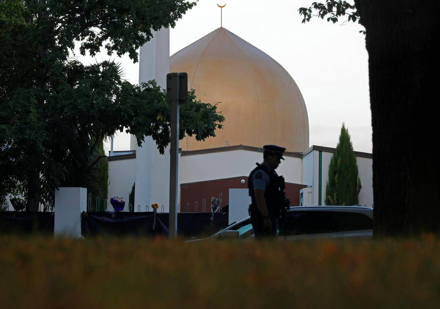 FILE - In this March 17, 2019, file photo, a police officer stands guard in front of the Al Noor mosque in Christchurch, New Zealand. The man authorities believe carried out the Christchurch mosque attacks is due to make his second court appearance via video link on Friday, April 4, 2019, although media photographs won't be allowed and reporting on the proceedings will be limited by New Zealand law. Fifty people died in the March 15 attacks on two mosques (AP Photo/Vincent Yu, File)