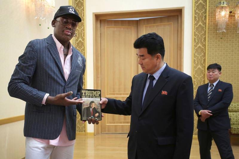 """FILE - In this June 15, 2017, file photo, former NBA basketball star Dennis Rodman presents a book titled """"Trump The Art of the Deal"""" to North Korea's Sports Minister Kim Il Guk in Pyongyang, North Korea. Rodman says he will travel to Singapore """"for the historical summit"""" between President Donald Trump and North Korea's Kim Jong Un, even though Trump says he wasn't invited.  (AP Photo/Kim Kwang Hyon, File)"""
