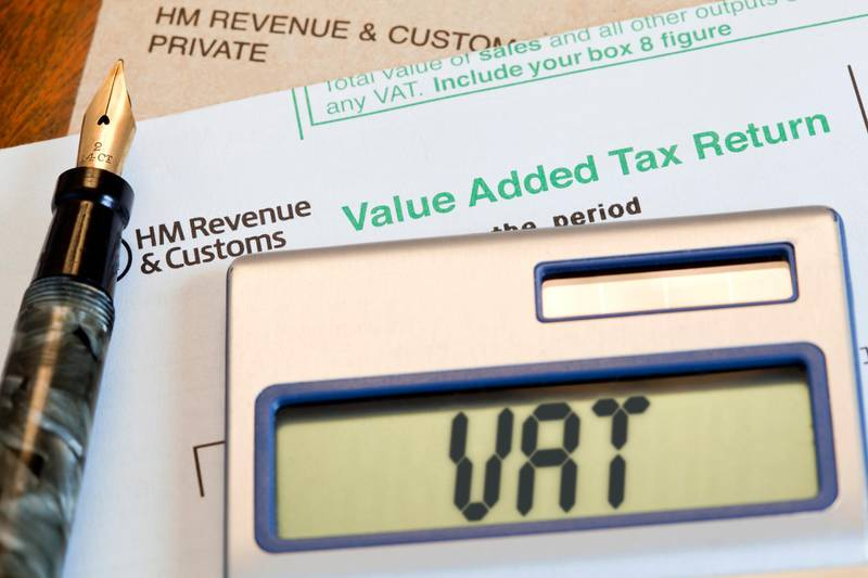 """""""UK VAT, Value Added Tax form, for Her Majestyaas Revenue & Customs, with a calculator, manilla brown envelope and antique fountain pen on a desktop. VAT, or Value added Tax, is a tax on the purchase price of goods and services. The tax is paid to the government by registered businesses and is the sale price of the goods or services, minus the cots of materials and other taxable inputs. In most cases this tax is paid quarterly per annum."""" Getty Images"""