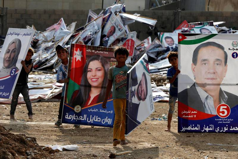 Children pose as they search for wood in parliamentary candidates' posters after parliament elections results were announced in Amman, Jordan November 12, 2020. REUTERS/Muhammad Hamed