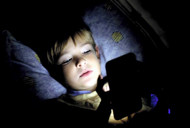 Boy using laptop on dark bedroom