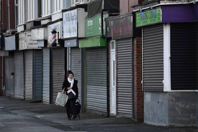 A woman walks past closed-down shuttered shops in Hull, in north-east England on November 30, 2020.   Hull will return to the England's highest coronavirus category, Tier 3, when England exits its second lockdown an re-enters a tiered system of toughened regional restrictions on December 2. Britain has been Europe's worst-hit country during the pandemic, recording more than 57,000 deaths from some 1.6 million cases. / AFP / Oli SCARFF