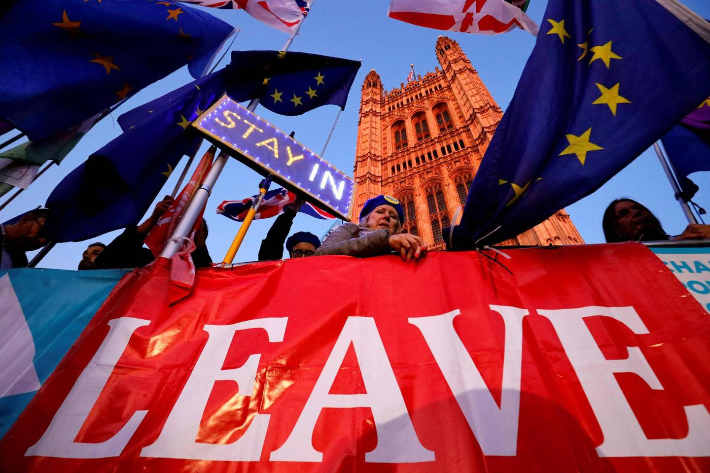 (FILES) In this file photo taken on October 22, 2019 Banners, Union and EU flags are displayed outside the Houses of Parliament in London on October 22, 2019, as MPs debate the second reading of the Government's European Union (Withdrawal Agreement) Bill.  The UK and European Union will on December 30 sign a mammoth trade pact to put the seal on their drawn-out Brexit divorce in the dwindling hours before they part ways definitively at the dawning of 2021. / AFP / Tolga Akmen / TO GO WITH STORY BY JITENDRA JOSHI